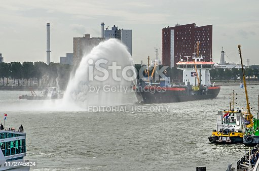 Rotterdam, The Netherlands, September 6, 2019: dredger Ecodelta creating an arch of water on the river Nieuwe Maas during the Wereldhavendagen (World Port Days) festival