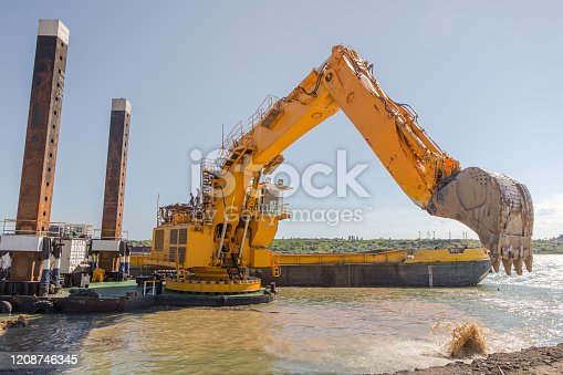 Dredging. A floating excavator drips soil from the seabed with a huge bucket