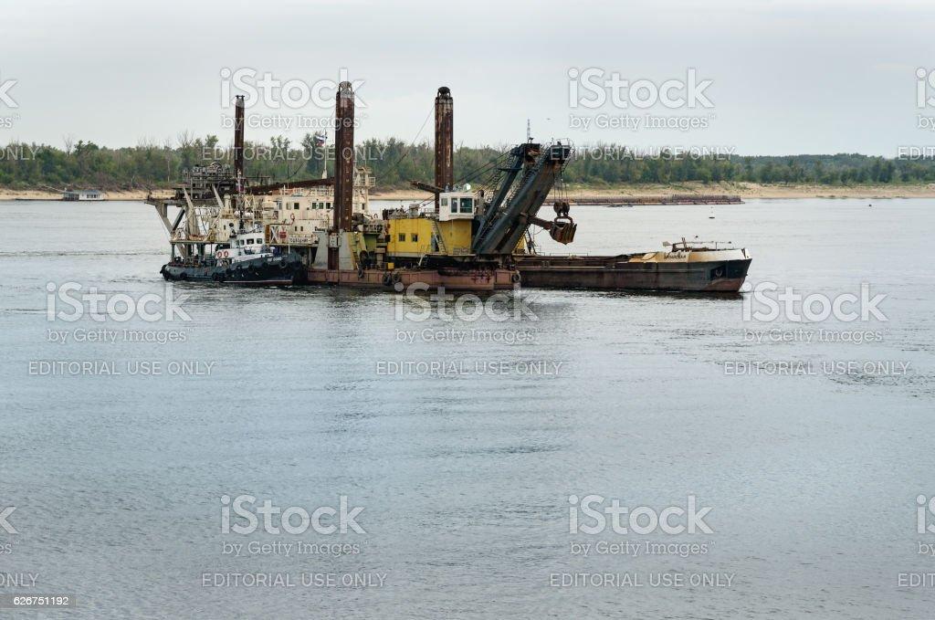 Dredging platform and cargo ship stock photo