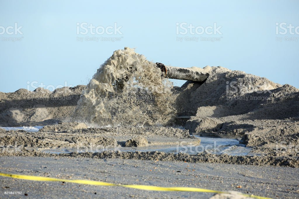 Dredging sand on the beach stock photo
