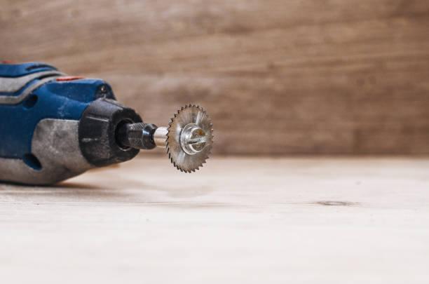 dremel werkzeug mit einer installierten kleine kreissäge auf einem holzbrett hintergrund. workshop. herstellung von holzprodukten. tischler-schneidwerkzeug - dremel zubehör stock-fotos und bilder