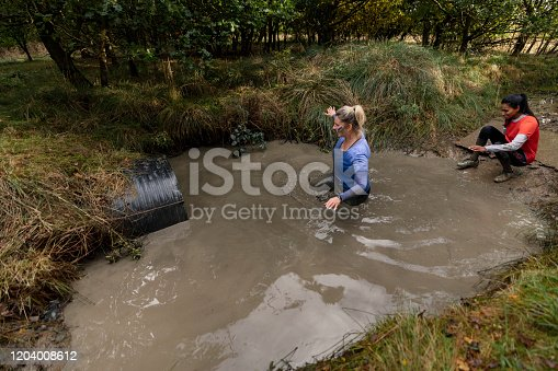Woman walking waist deep in water to tunnel in outdoor obstacle course, determination, achievement, endurance
