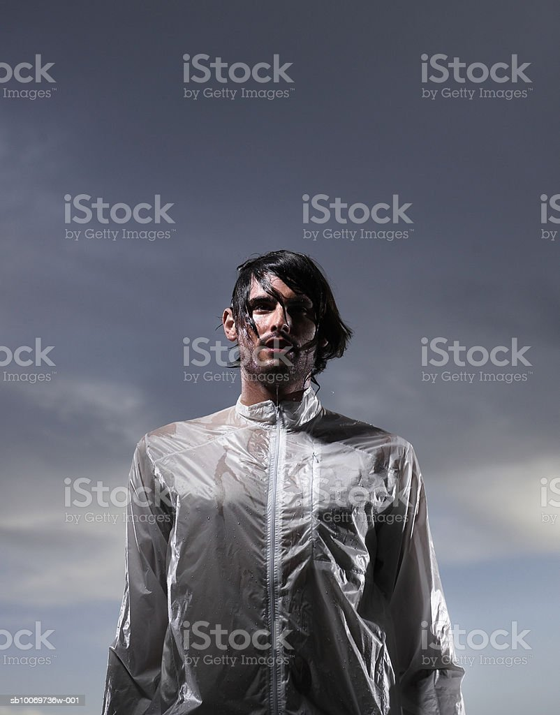 Drenched young man at dusk, low angle view royalty-free stock photo