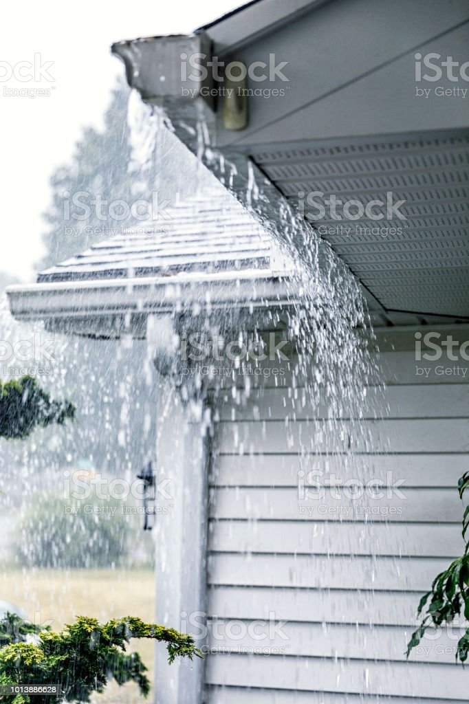 Drenching downpour rain storm water is rushing and splashing off the...