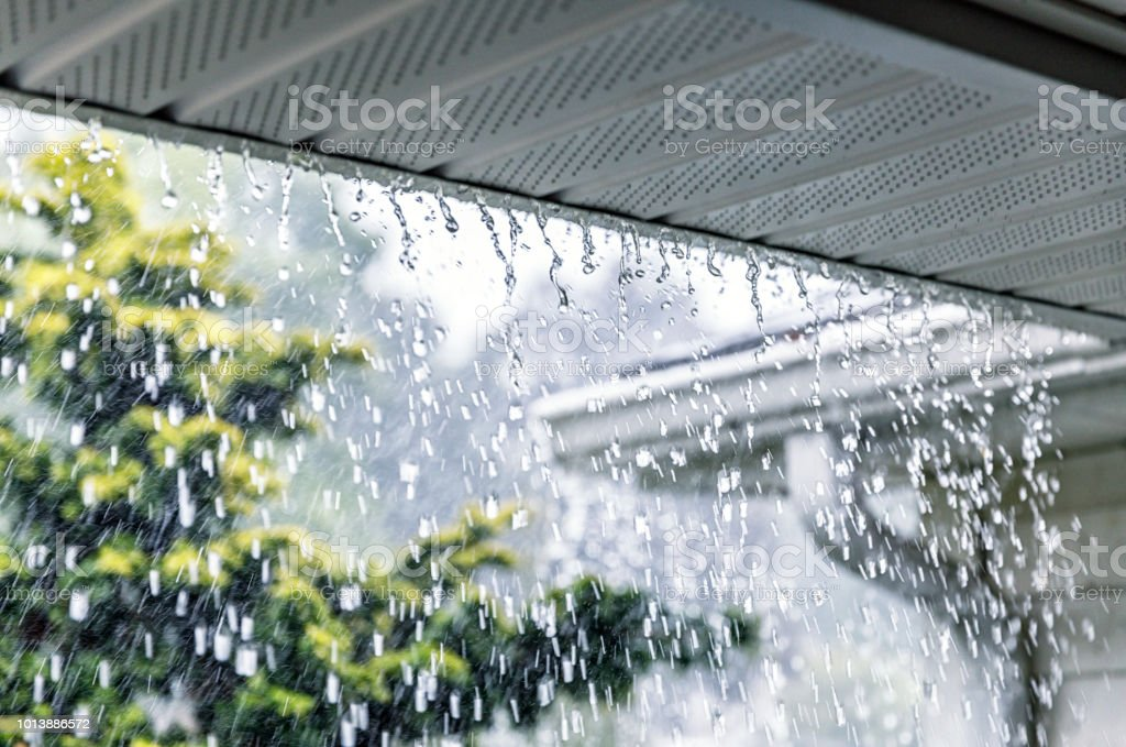 Drenching downpour rain storm water is rushing and splashing over the...