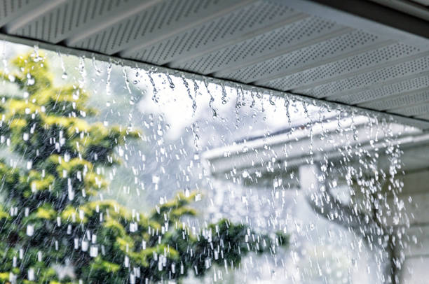 Drenching Rain Storm Water Flooding Over Roof Gutter stock photo