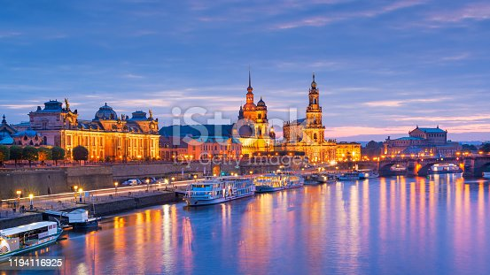 Dresden, Germany cityscape of cathedrals over the Elbe River at dusk.