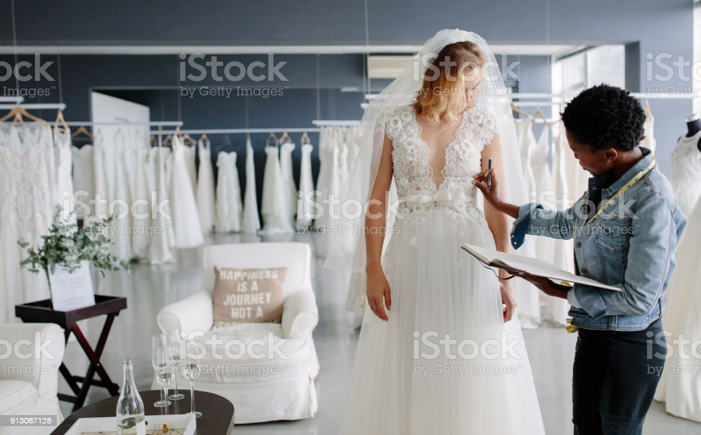 Dress designer fitting bridal gown to woman in boutique stock photo