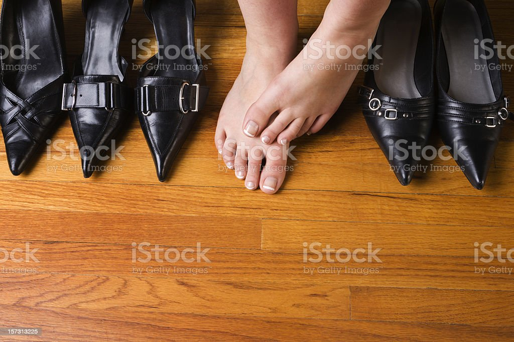 Dress Shoes and High Heels with Woman's Feet on Floor stock photo