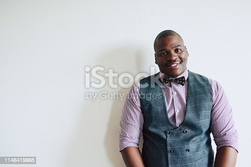 Studio shot of a stylishly dressed young businessman against a grey background
