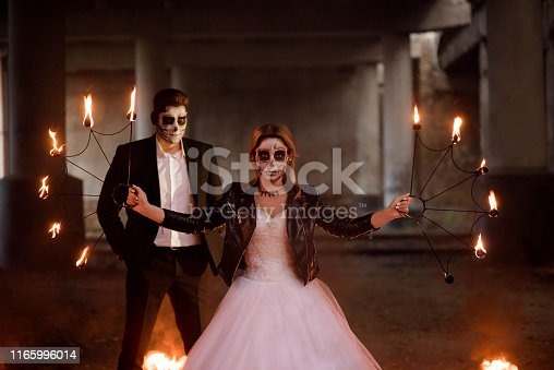 Dressed in wedding clothes romantic zombie couple in the dark