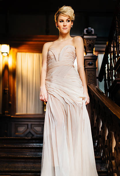 Dressed up woman in evening gown walking stairway to ballroom Young woman in evening gown walking down old wooden stairway to the ballroom with a slight naughty smile. Edited 50s/60s Technicolor style retro colors. evening wear stock pictures, royalty-free photos & images
