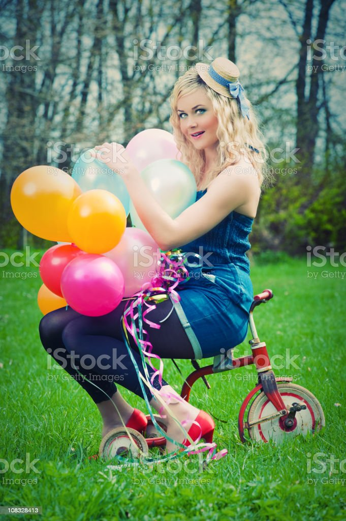 Dressed up woman with balloons and a child bike royalty-free stock photo