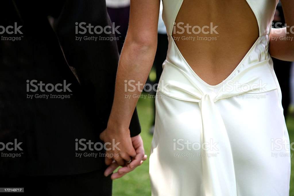 Dressed-up couple holding hands walking to the aisle royalty-free stock photo