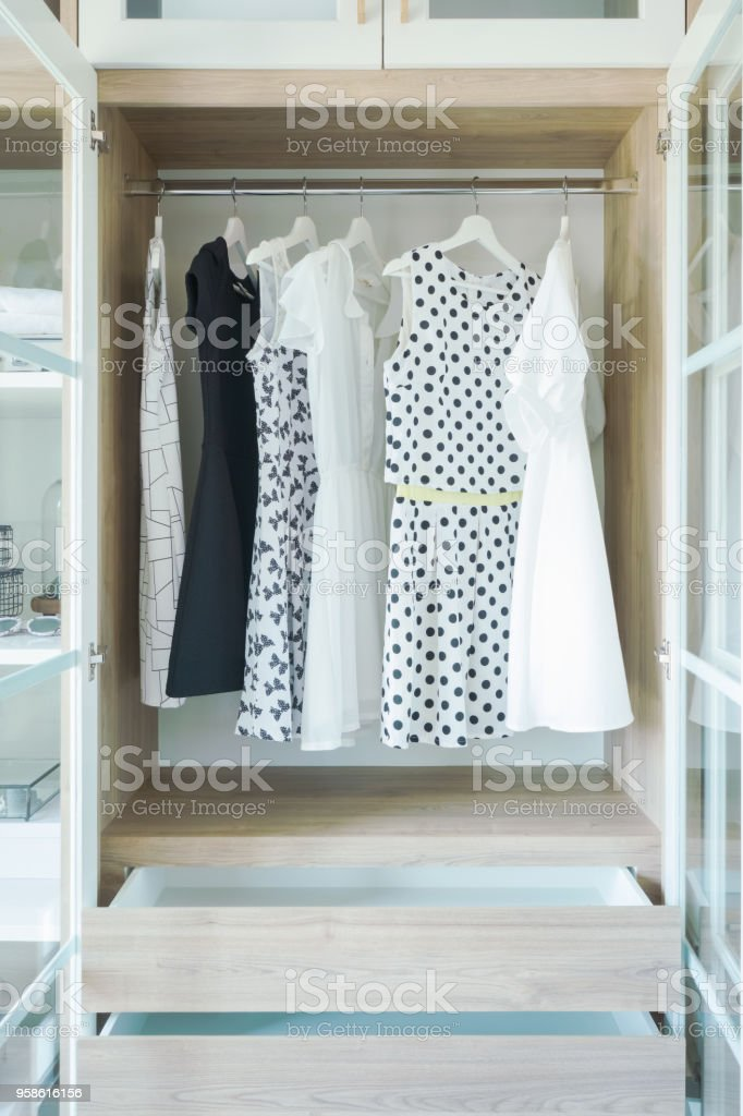 Dresses hanging on rail in wooden closet stock photo