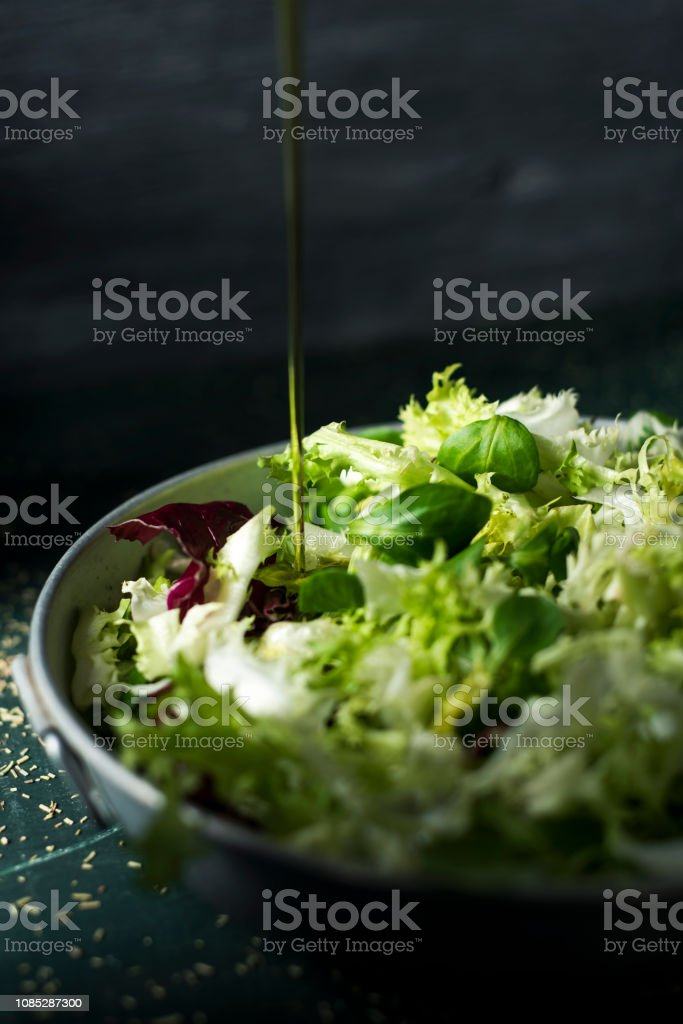 dressing a green salad with olive oil stock photo