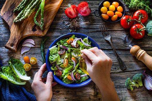 Dressing fresh organic vegetables salad with olive oil