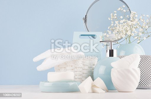 1056636898 istock photo Dressing table with circle mirror, cosmetic silver accessories and white small flowers in ceramic pastel blue vase on white wood board, closeup. 1068426202