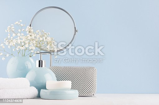 1056636898 istock photo Dressing table with circle mirror, cosmetic silver accessories and white small flowers in ceramic pastel blue vase on white wood board. 1124374926
