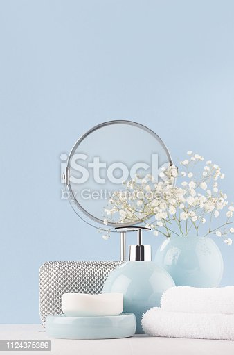 1056636898 istock photo Dressing table with circle mirror, cosmetic silver accessories and white small flowers in ceramic pastel blue vase on white wood board, closeup, vertical. 1124375386