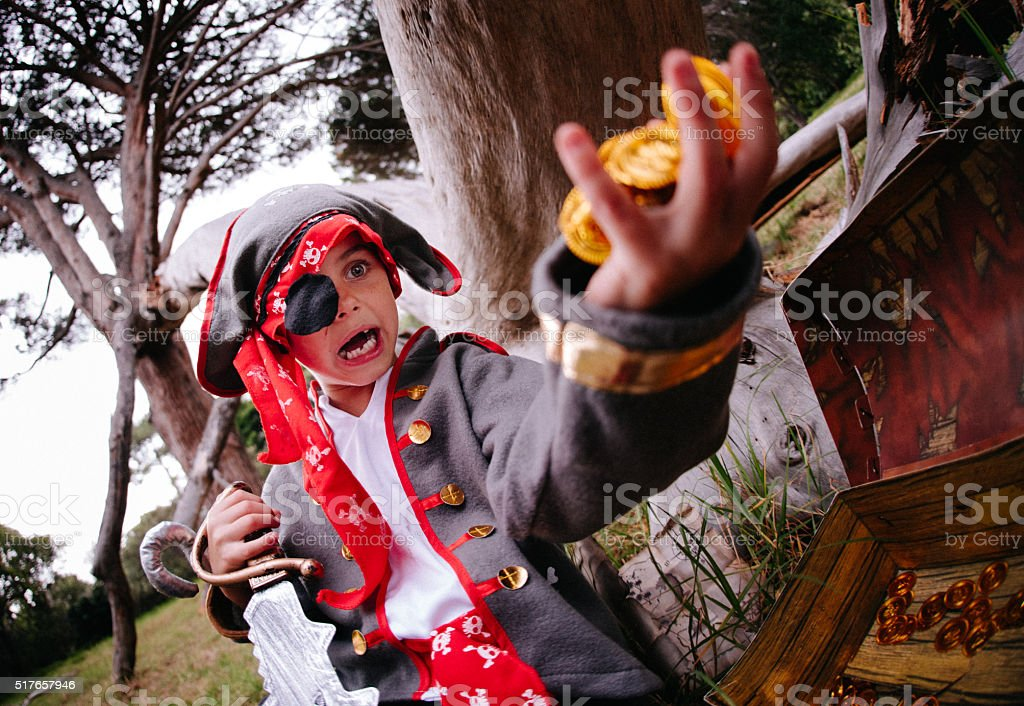 Dressing up Pirate child finding gold coins in treasure chest stock photo