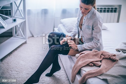 Young woman sitting at the bed in her bedroom, getting ready for work, dressing up her stockings.