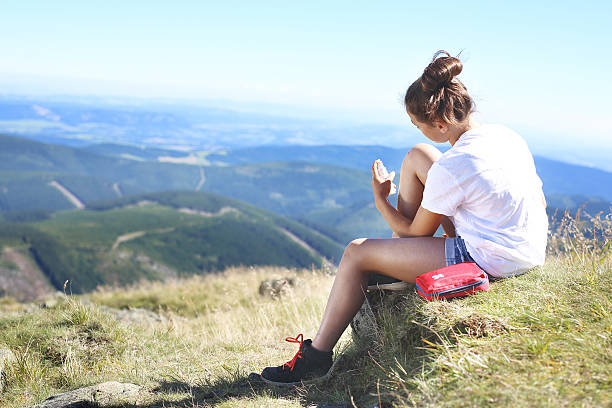 Dressing wounds. Tourist disinfects the wound on his knee while sitting on the slope of a mountain trail. antiseptic stock pictures, royalty-free photos & images
