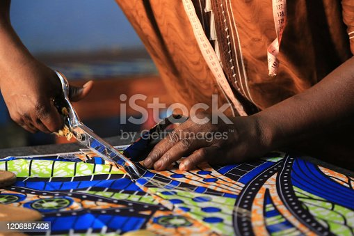 istock Dressmaker cutting fabric with a pair of scissors. Lome. Togo. West Africa. 1206887408