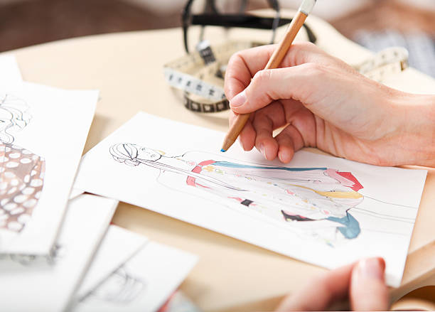 Dressmaker is drawing a fashion sketch Dressmaker is drawing a fashion sketch. Close up of the hands fashion designer stock pictures, royalty-free photos & images