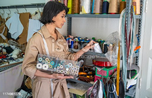 Dressmaker seamstress working with sewing threads at fashion designer studio