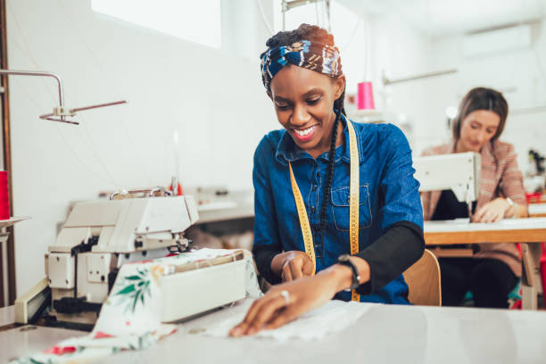 Dressmaker woman working with sewing machine stock photo