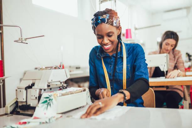 Modista mujer trabajando con máquina de coser - foto de stock
