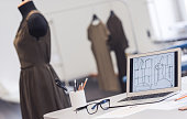 Dressmaker's workplace. A desk with a laptop, sketches and eyeglasses on it, dress models on background