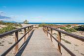 Drewniany most prowadzący do piaszczystej plaży, w oddali morze Śródziemne , piasek i rośliny . Gran Alacant, Hiszpania.