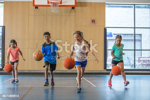 A multi-ethnic group of elementary age children are dribbling basketballs down the court in the gym.