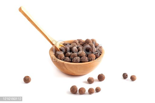 Dried allspice in the wooden bowl, isolated on white background.