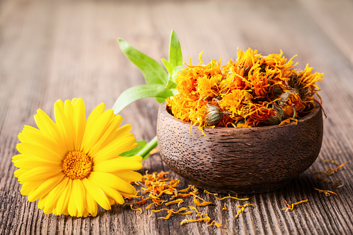 Dried and fresh marigold (calendula) flowers in a bowl on wooden rustic background space for text close-up.