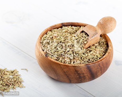 Dried Anise Seed or Aniseed in wooden bowl on white background.