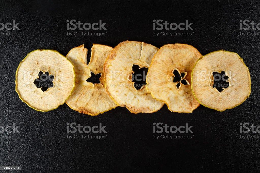 Getrocknete Apfelscheiben auf schwarzem Hintergrund – Foto