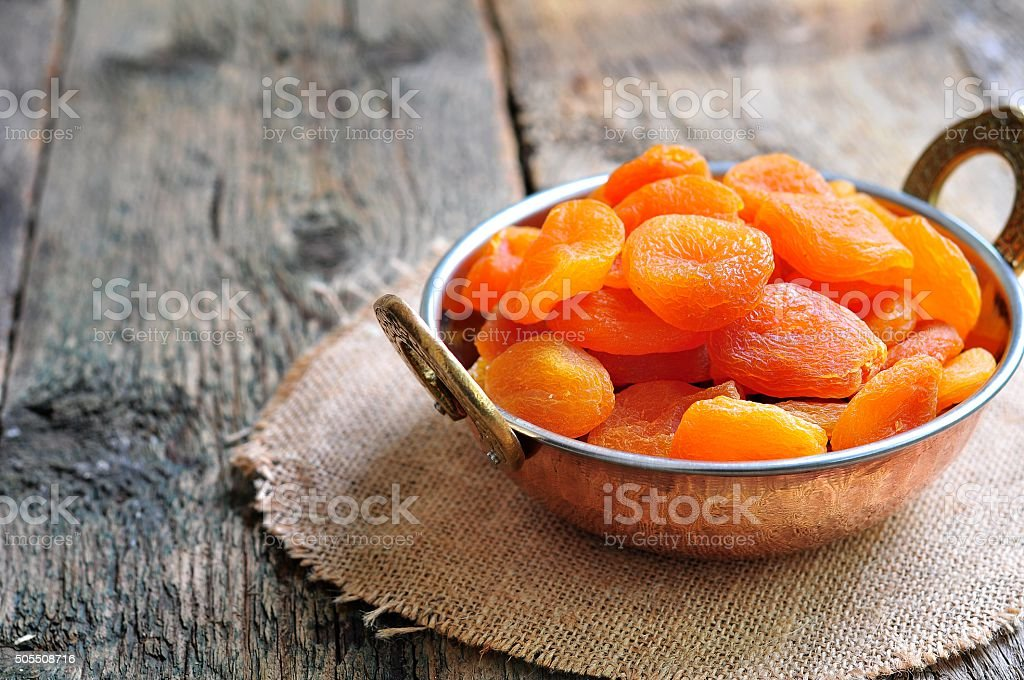 Dried apricot in a copper bowl Dried apricot in a copper bowl on the old wooden background Appetizer Stock Photo