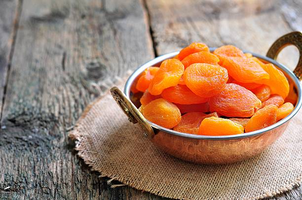 dried apricot in a copper bowl - dried fruit stock photos and pictures