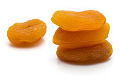 Three dried apricots in pile and one isolated on white background