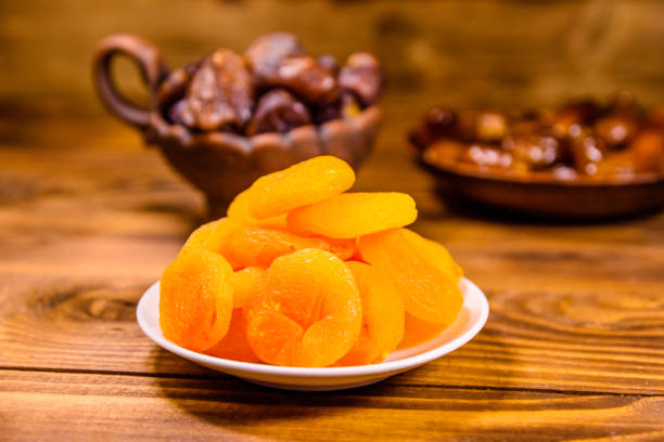 Abricots secs et fruits de date sur la table en bois - Photo