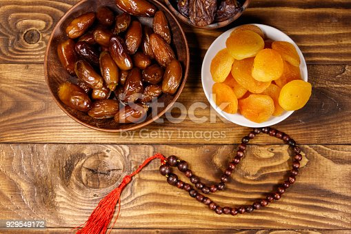 istock Dried apricots and dates fruit with wooden rosary on wooden table. Top view 929549172