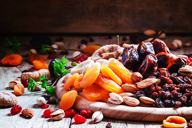 dried apricots, dates, raisins and various nuts - dried fruit stock photos and pictures