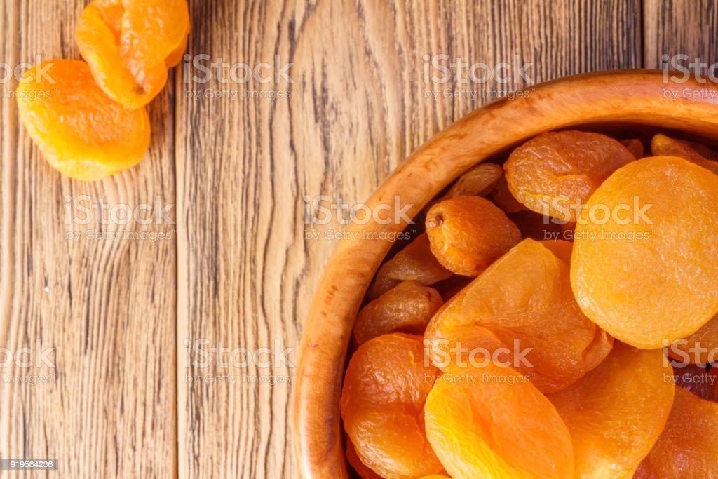 Abricots secs, les fruits secs dans une plaque de bois. Style rustique. Alimentation saine. Place pour le texte. Kaisa. - Photo