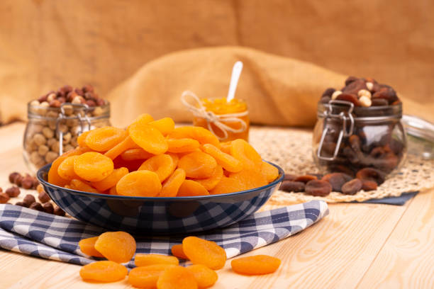 Dried apricots in a blue plate on the wooden table.