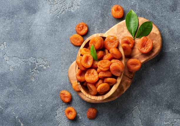 gedroogde abrikozen op grijze achtergrond. ruimte voor tekst kopiëren. bovenaanzicht. - gedroogd voedsel stockfoto's en -beelden