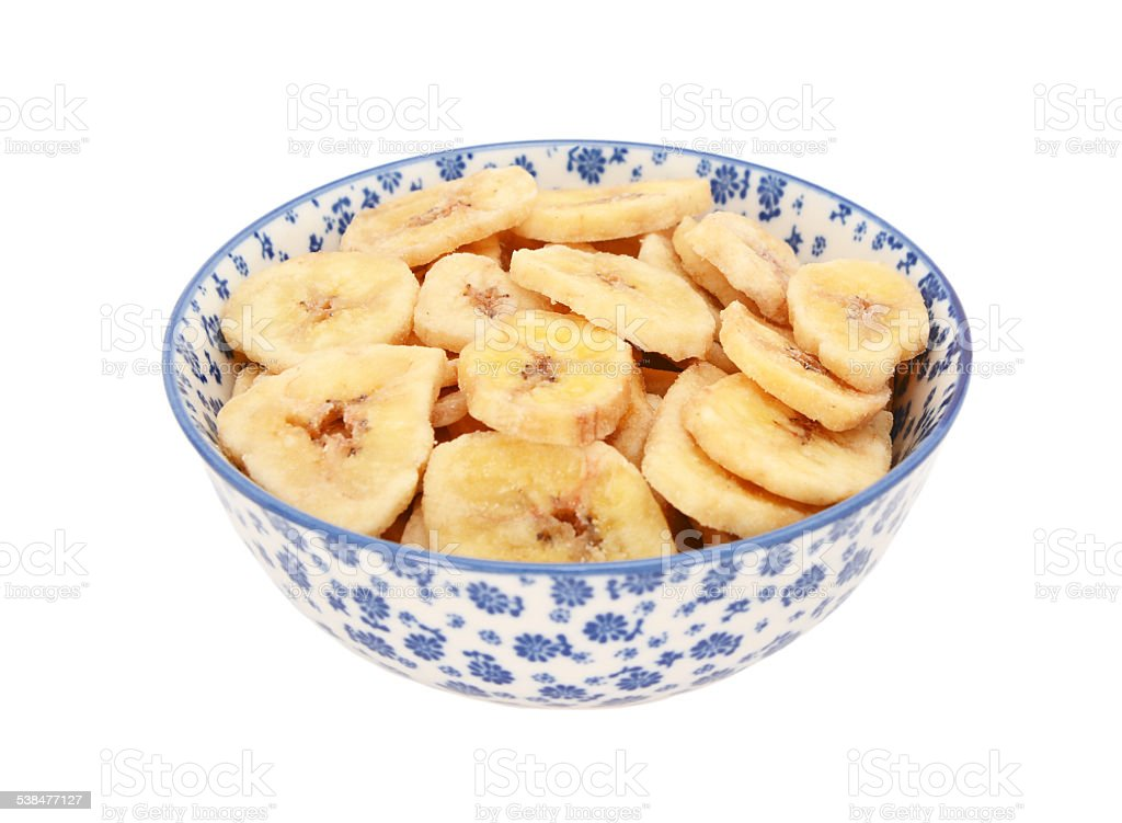Dried banana chips in a blue and white china bowl stock photo