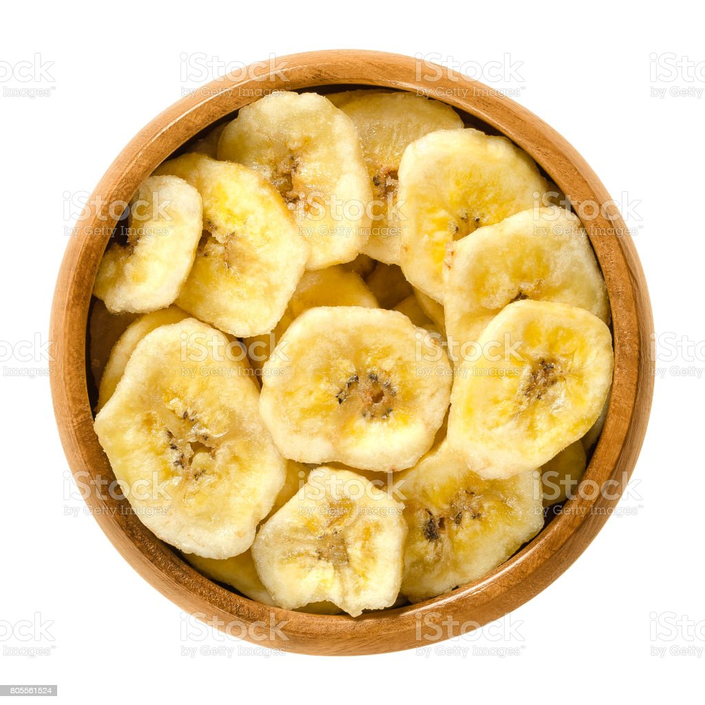 Dried banana chips in wooden bowl over white stock photo